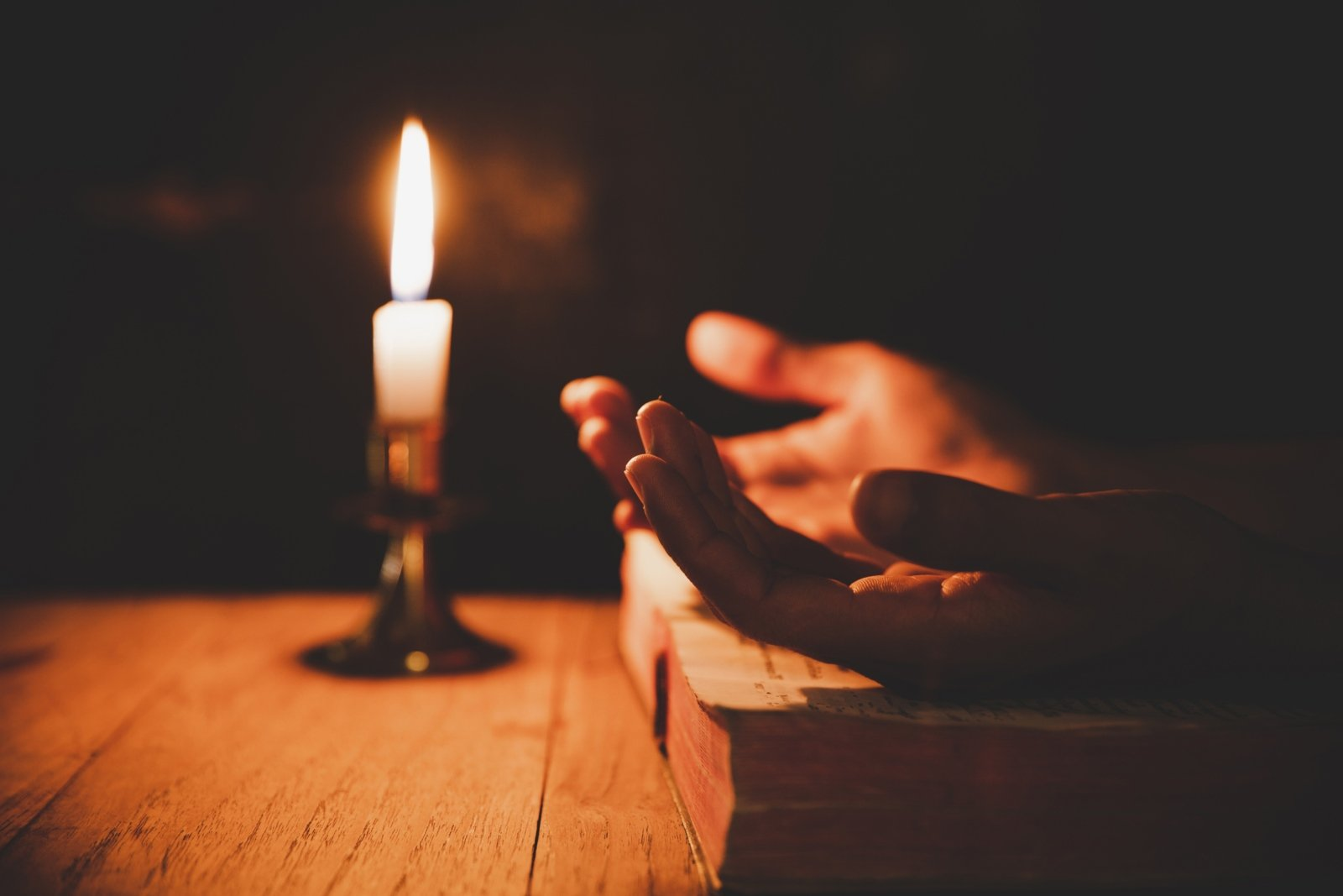 close-up-man-s-hand-is-praying-church-with-lit-candle (c) canva.com